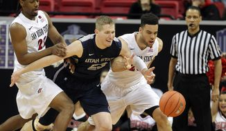 San Diego State's Josh Davis, left and JJ O'Brien go after a loose ball with Utah State's Kyle Davis during the first half of an NCAA college basketball game in the quarterfinals of the Mountain West Conference tournament Thursday, March 13, 2014, in Las Vegas. (AP Photo/Isaac Brekken)
