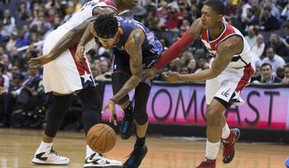 Washington Wizards forward Al Harrington, left, and guard Bradley Beal, right, defend Charlotte Bobcats guard Chris Douglas-Roberts during the first half of an NBA basketball game Wednesday, March 12, 2014, in Washington. (AP Photo/ Evan Vucci)