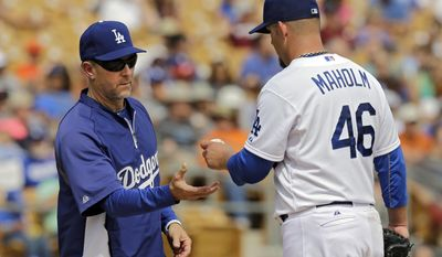 Los Angeles Dodgers bench coach Tim Wallach, left, takes the ball from starting pitcher Paul Maholm in the third inning of a spring exhibition baseball game against the Cincinnati Reds, Thursday, March 13, 2014, in Glendale, Ariz. Wallach was acting manager for the game. (AP Photo/Mark Duncan)