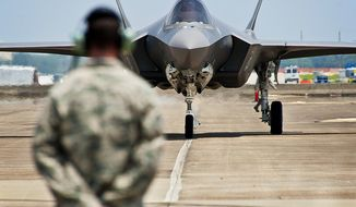 U.S. Air Force Tech. Sgt. Brian West watches an Air Force F-35 Lightning II joist strike fighter aircraft approach for the first time July 14, 2011, at Eglin Air Force Base, Fla. (U.S. Air Force photo by Samuel King Jr.) ** FILE **