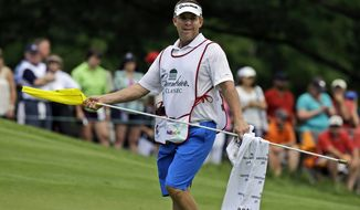 FILE - In this July 4, 2013, file photo, New Orleans Saints coach Sean Payton carries the flag for golfer Ryan Palmer on the eighth hole during the first round of the Greenbrier Classic PGA tour golf tournament at the Greenbrier in White Sulphur Springs, W.Va. The Saints announced Thursday, March 13, 2014, that the team will split their 2014 training camp between the team's practice facility in Metarie, La., and The Greenbrier in White Sulphur Springs. (AP Photo/Steve Helber,File)