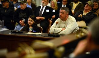 Nine-year-old Shyanne Roberts, left, a nationally sponsored competitive shooter from Franklinville NJ, speaks against the proposed limit on magazine rounds at the statehouse. Her father Dan is at right. (AP Photo/Northjersey.com, Michael Karas)