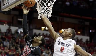 San Diego State's Skylar Spencer blocks a shot from UNLV's Deville Smith during the first half of an NCAA college basketball game in the semifinals of the Mountain West Conference tournament Friday, March 14, 2014, in Las Vegas. (AP Photo/Isaac Brekken)