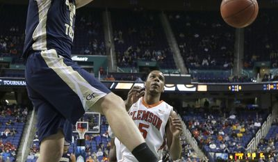 Georgia Tech's Daniel Miller, front, dunks as Clemson's Jaron Blossomgame, back, watches during the first half of a second round NCAA college basketball game at the Atlantic Coast Conference tournament in Greensboro, N.C., Thursday, March 13, 2014. (AP Photo/Gerry Broome)