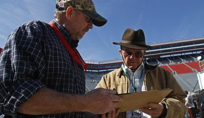 Car owner Jack Roush, right, signs an autograph before practice for the NASCAR Sprint Cup series auto race at Bristol Motor Speedway on Friday, March 14, 2014, in Bristol, Tenn. (AP Photo/Wade Payne)