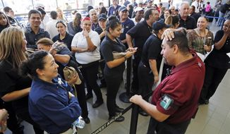 FILE - This Nov. 11, 2013 file photo shows airport employees preparing to clear security as they wait to reopen after a shooting at Terminal 3 caused a shutdown of Los Angeles International Airport. Thousands of Los Angeles International Airport workers had no idea what to do when a gunman opened fire last year or how to help because they were inadequately trained to deal with an emergency, according to a union report obtained Friday March 14, 2014. AP Photo/Reed Saxon, file)