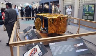 FILE - In this May 30, 2013 file photo, visitors and staff at the U.S. Geological Survey's Earth Resources Observation and Science Center, EROS, gather near a scale model of the Landsat 7 satellite. The facility is helping in the international search for a missing Malaysian jetliner. EROS collects, archives and makes available for download more than 400 data-filled images of the Earth each day. The images coming from EROS have not produced any solid leads in the case of the missing plane, but the center's Disaster Response Coordinator Brenda Jones said she hopes the center's work eventually will help lead to answers. (AP Photo/Dirk Lammers, File)