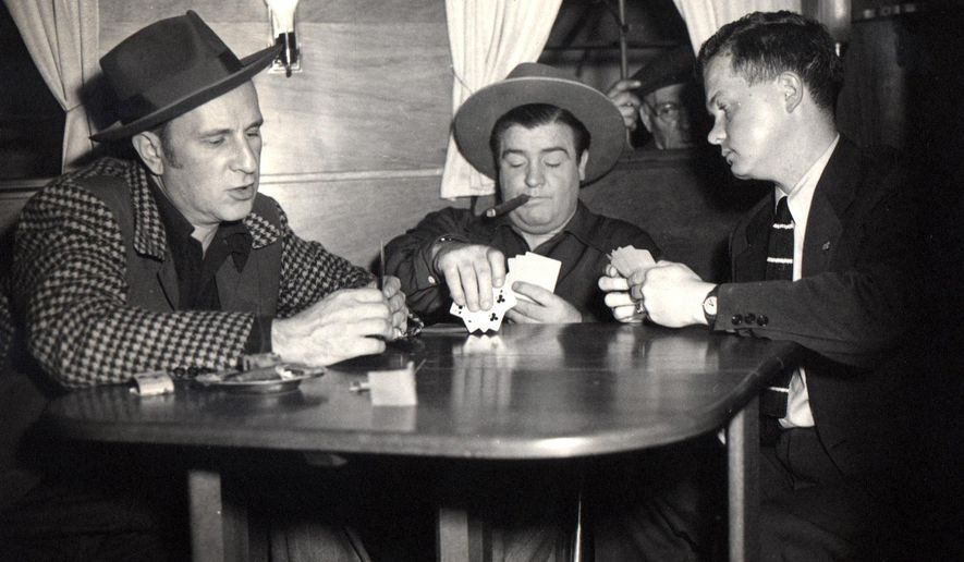 """FILE - In this circa 1945 file photo provided by Associated Press reporter Bob Thomas, right, plays poker with legendary comedians Bud Abbott, left, and Lou Costello, during an interview. When Thomas began writing a Hollywood column for The AP in 1944, there were 500 journalists covering the movie scene. Fresh, newsy interviews were hard to come by, so he began writing """"participation stories.""""  Thomas died of age-related illnesses Friday, March 14, 2014 at his Encino, Calif., home, his daughter Janet Thomas said. He was 92. (AP Photo/Courtesy Bob Thomas, file)"""