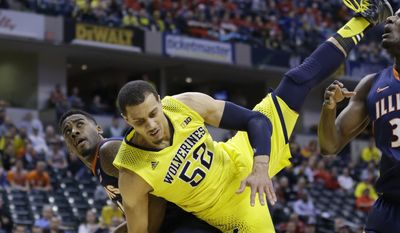 Michigan forward Jordan Morgan falls to the floor after scoring a basket against Illinois guard Rayvonte Rice, left, in the first half of an NCAA college basketball game in the quarter finals of the Big Ten Conference tournament Friday, March 14, 2014, in Indianapolis. (AP Photo/Michael Conroy)