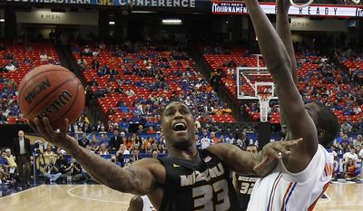 Missouri guard Earnest Ross (33) shoots against Florida forward Dorian Finney-Smith (10) during the second half of an NCAA college basketball game in the quarterfinal round of the Southeastern Conference men's tournament, Friday, March 14, 2014, in Atlanta. (AP Photo/Steve Helber)