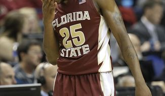 Florida State's Aaron Thomas (25) wipes his face as he walks up the court during the second half of an NCAA college basketball game against Virginia in the quarterfinal round of the Atlantic Coast Conference tournament in Greensboro, N.C., Friday, March 14, 2014. Virginia won 64-51. AP Photo/Gerry Broome)