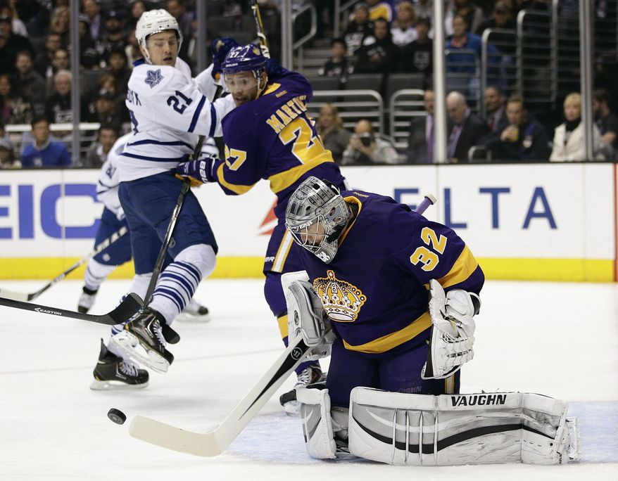 Los Angeles Kings goalie Jonathan Quick, center, makes a save as Toronto Maple Leafs' James van Riemsdyk (21) and  Kings' Alec Martinez (27) watch during the first period of an NHL hockey game on Thursday, March 13, 2014, in Los Angeles. (AP Photo/Jae C. Hong)