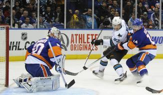 New York Islanders goalie Evgeni Nabokov (20) and Thomas Hickey (14) defend against San Jose Sharks' Matt Nieto (83)  in the first period of an NHL hockey game on Friday, March 14, 2014, in Uniondale, N.Y. (AP Photo/Kathy Kmonicek)