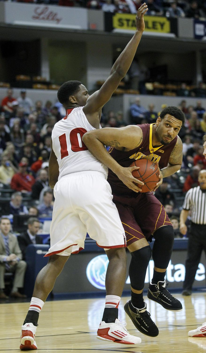 Minnesota forward Maurice Walker drives the ball around Wisconsin forward Nigel Hayes (10) in the first half of an NCAA college basketball game in the quarterfinals of the Big Ten Conference tournament Friday, March 14, 2014, in Indianapolis. (AP Photo/Kiichiro Sato)
