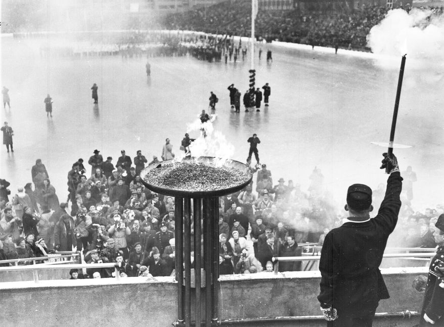 **FILE** Egil Nansen, grandson of the famous Norwegian explorer, holds aloft the torch after lighting the Olympic Flame, at Bislett Stadium, Oslo, on Feb. 15, 1952. The ceremony was part of the official opening of the sixth winter Olympics. (AP Photo)