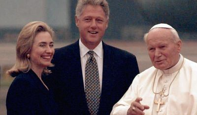 **FILE** Pope John Paul II gestures to the crowd as he is greeted by President Bill Clinton and his wife Hillary during their arrival at Newark International Airport in Newark, N.J., on Oct. 4, 1995. (Associated Press)