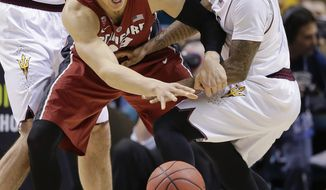 Stanford's Dwight Powell, left, and Arizona State's Jahii Carson vie for a loose ball in the first half of an NCAA college basketball game in the Pac-12 men's tournament quarterfinals, Thursday, March 13, 2014, in Las Vegas. (AP Photo/Julie Jacobson)