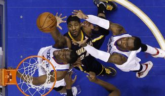 Philadelphia 76ers' Jarvis Varnado, left, and Tony Wroten, right, battle for a rebound against Indiana Pacers' Paul George during the first half of an NBA basketball game on Friday, March 14, 2014, in Philadelphia. (AP Photo/Matt Slocum)