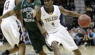 Toledo's Justin Drummond (4) drives past Eastern Michigan's Darell Combs (25) as Matt Smith (43) blocks in the first half of an NCAA college basketball game at the Mid-American Conference tournament Friday, March 14, 2014, in Cleveland. (AP Photo/Tony Dejak)