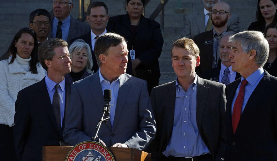 Then-Colo. Gov. John Hickenlooper, second from left, flanked at right by U.S. Senators Mark Udall, far right, and Michael Bennet,  and backed by several Colorado mayors, speaks to members of the media on the state Capitol steps during a visit from Secretary of U.S. Housing and Urban Development (HUD) Shaun Donovan, left, in Denver, Friday, March 14, 2014. (AP Photo/Brennan Linsley)