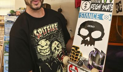 In this photo taken on Jan. 22, 2014, skateboarder Chris Cole displays the bottom of his latest finished skateboard with its multiple sponsors' decals he put together in his garage workshop at his home in San Marcos, Calif. Cole has cashed enough six-figure contest checks and done well enough from shoe deals to afford a nice life in a million-dollar house on a plot big enough for his own backyard skate park.  (AP Photo/Lenny Ignelzi)