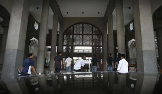 Muslim men arrive at the Kuala Lumpur International Airport Mosque for afternoon prayers where a special prayer session will be offered for the missing Malaysia Airlines flight MH370, Friday, March 14, 2014 in Sepang, Malaysia. Vietnam says it has downgraded but not stopped its search for the missing jetliner in the South China Sea and has been asked by Malaysian authorities to consider sending planes and ships to the Strait of Malacca. The statement Friday is a sign that the focus of the search effort is switching to the west of Malaysia, to the strait and further west into the Indian Ocean. (AP Photo/Wong Maye-E)