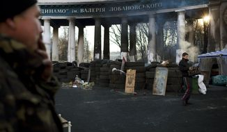A man, at right, clears bottles at a barricade near the entrance to the stadium of Dynamo Kyiv soccer club in Kiev, Ukraine, Wednesday, March 12, 2014. Ukraine's domestic soccer league will resume play on March 15, after a two-week postponement because of the turmoil in the country. (AP Photo/David Azia)