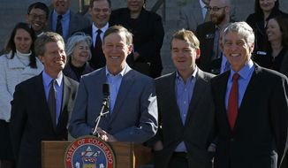 Colo. Gov. John Hickenlooper, second from left, flanked at right by U.S. Senators Mark Udall, far right, and Michael Bennet,  and backed by about a dozen Colorado mayors, speaks to members of the media on the state Capitol steps during a visit from Secretary of U.S. Housing and Urban Development (HUD) Shaun Donovan, left, in Denver, Friday, March 14, 2014. Secretary Donovan  announced Friday that Colorado is getting an additional $199 million from the federal government to help communities devastated by September's historic floods. (AP Photo/Brennan Linsley)
