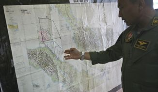 """Lt. Col Bambang Sudewo, commander of the 5th Air Squadron """"Black Mermaids,"""" examines a map following a search operation for the missing Malaysia Airlines Boeing 777 that was conducted over the Strait of Malacca, at Suwondo air base in Medan, North Sumatra, Indonesia, Friday, March 14, 2014. The jetliner vanished nearly a week ago with 239 people aboard. (AP Photo/Binsar Bakkara)"""