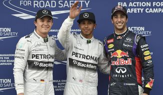 Mercedes driver Nico Rosberg of Germany, left, his team mate Lewis Hamilton of Britain, center, and Red Bull driver Daniel Ricciardo of Australia, right, pose for a photo after taking pole positions after qualifying at Albert Park ahead of the Australian Formula One Grand Prix in Melbourne, Australia, Saturday, March 15, 2014. (AP Photo/Ross Land)