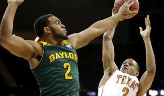 Baylor's Rico Gathers, left, blocks a shot by Texas' Demarcus Holland, right, during the second half of an NCAA college basketball game in the Big 12 men's tournament Friday, March 14, 2014, in Kansas City, Mo. Baylor won 86-69. (AP Photo/Charlie Riedel)