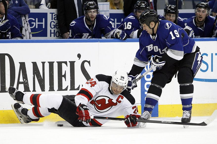 Tampa Bay Lightning right wing B.J. Crombeen (19) and New Jersey Devils defenseman Bryce Salvador (24) vie for the puck during the second period of an NHL hockey game Saturday, March 15, 2014, in Tampa, Fla. (AP Photo/Brian Blanco)
