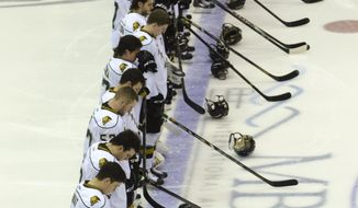 London Knights hockey players stand during a moment of silence for the late Saginaw Spirit player Terry Trafford before an Ontario Hockey League game Saturday, March 15, 2014, in Saginaw, Mich.  Police have said Trafford died of self-inflicted asphyxiation inside his vehicle parked outside a store in Michigan. The Toronto native's body was found March 12. He disappeared eight days earlier after receiving discipline from the club.  (AP Photo/The Saginaw News, Tim Goessman  LOCAL TV OUT  LOCAL INTERNET OUT