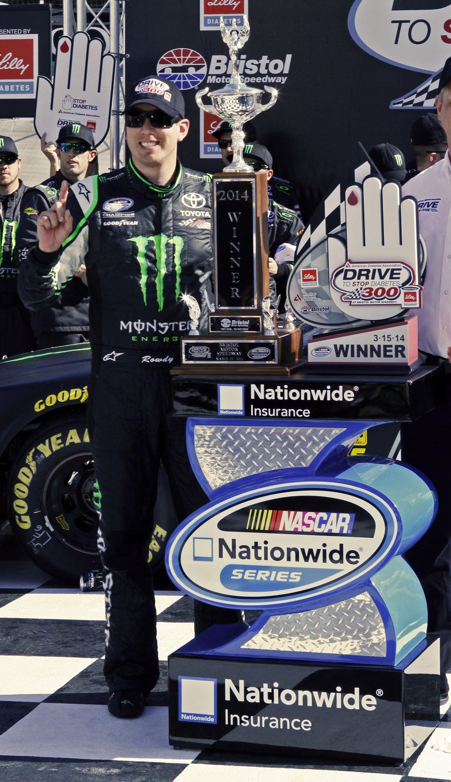 Driver Kyle Busch (54) stand with the trophy after winning the NASCAR Nationwide series auto race at Bristol Motor Speedway on Saturday, March 15, 2014, in Bristol, Tenn. (AP Photo/Wade Payne)