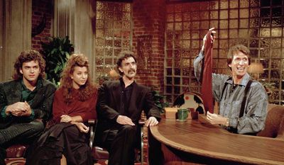 """FILE - In this Sept. 24, 1986 file photo, comedian David Brenner hosts avant garde fusion musician Frank Zappa, center, and his children, Dweezil, left, and Moon Unit, during a taping of Brenner's """"Nightlife"""" talk show in New York. Brenner holds a necktie given to Frank Zappa upon entering a restaurant earlier in the day. On Saturday, March 15, 2014, publicist Jeff Abraham announced Brenner has died at the age of 78. (AP Photo/David Bookstaver)"""
