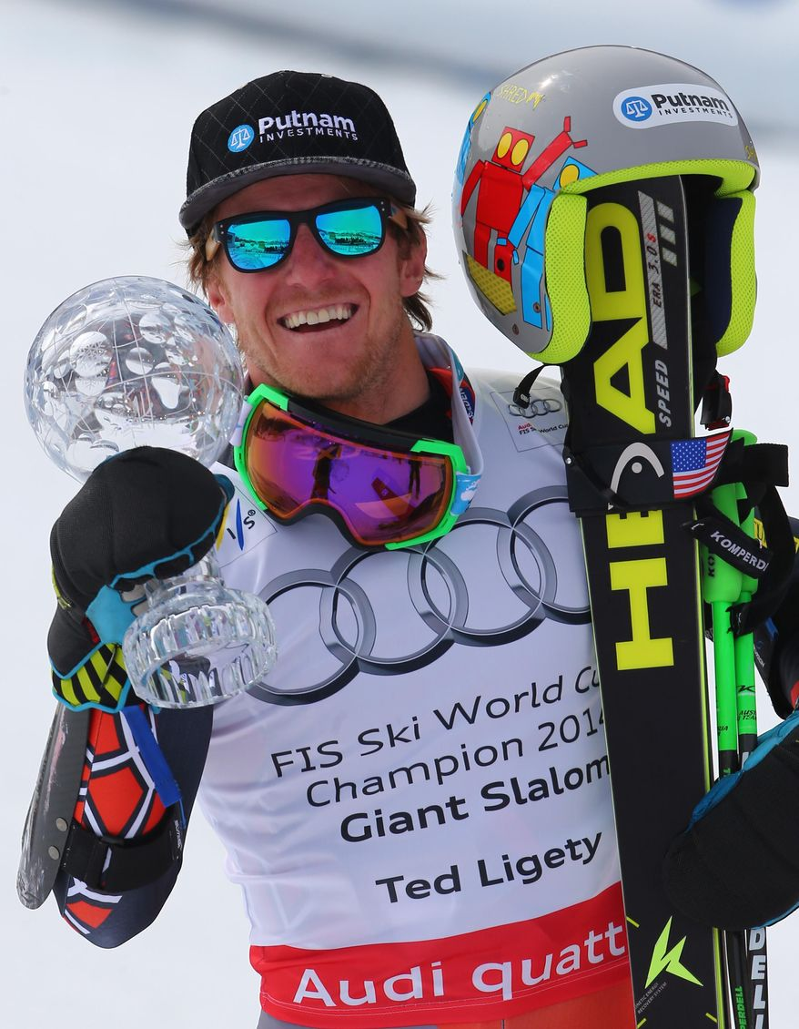 Ted Ligety, of the United States, holds up his trophy after winning an Alpine Ski men's giant slalom at the World Cup finals, in Lenzerheide, Switzerland, Saturday, March 13, 2013. (AP Photo/Marco Trovati)