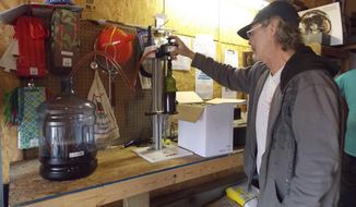ADVANCE FOR SUNDAY, MARCH 16 AND THEREAFTER - In this Monday, March 10, 2014 photo, Rodney Cox siphons a returning flavor of Cox Juice wine, wineberry, from its storage container to a wine bottle for eventual sale at the winery in Bunker Hill, W.Va.  (AP Photo/The Journal, Samantha Cronk)