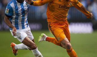 Real Madrid's Cristiano Ronaldo, right, duels for the ball against CF Malaga's Marcos Alberto Angeleri, left, during a Spanish La Liga soccer match at La Rosaleda stadium in Malaga, Spain, Saturday March 15, 2014. (AP Photo/Daniel Tejedor)