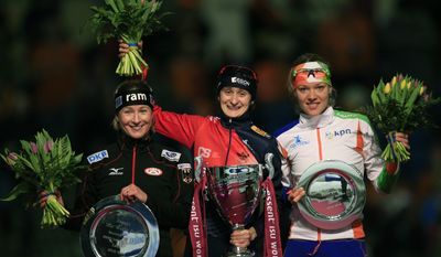 Martina Sablikova of the Czech Republic, center, holds the trophy as she poses with second place Claudia Pechstein of Germany, left, and third place Yvonne Nauta of the Netherlands, right, on the podium after the women's 3000-meter speedskating race at Thialf skating arena, Saturday, March 15, 2014, in Heerenveen, northern Netherlands. (AP Photo/Peter Dejong)