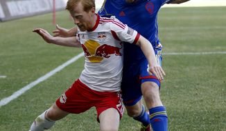 New York Red Bulls defender Richard Eckersley, left, protects the ball while defending against Colorado Rapids midfielder Dillon Powers during the first half of an MLS soccer game, Saturday, March 15, 2014, in Harrison, N.J. (AP Photo/Julio Cortez)