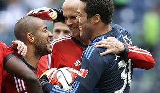 Toronto FC's Jermain Defoe, left, celebrates with goalkeeper Julio Cesar, right, and midfielder Michael Bradley, center, after they defeated the Seattle Sounders 2-1 in an MLS soccer match on Saturday, March 15, 2014, in Seattle. (AP Photo/Ted S. Warren)
