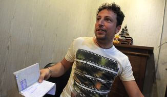In this March 12, 2014 photo, Italian Luigi Maraldi whose stolen passport was used by a passenger boarding a missing Malaysia Airlines plane, shows his passport as he speaks to a reporter at Phuket police station in Phuket province, southern Thailand. Maraldi lost his passport when he hired a motorbike on Phuket last year. When he returned to the shop to retrieve his passport, he was told it had been given away to someone who looked just like him. His passport, along with another stolen in Phuket two years earlier, was used to board the ill-fated flight from Kuala Lumpur to Beijing undetected, revealing startling shortcomings in the security of international travel. Interpol said it maintains a global database of 40 million lost or stolen travel documents. The organization said only a handful of countries actually check the database before allowing passengers to board international flights. Malaysia and Thailand are not among them. (AP Photo/Sakchai Lalit)