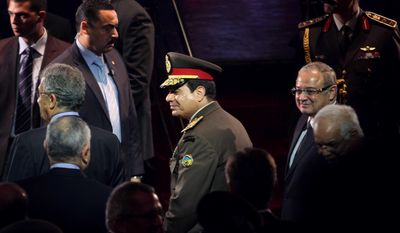 In this Thursday, March 14, 2014 photo, Egypt's Defense Minister, Field Marshal Abdel-Fattah el-Sissi, center, attends a gala event at the Cairo Opera House. Earlier in the day, the former chief of staff of the Egyptian armed forces, Gen. Sami Anan, declared that he would not run for president, as the public had anticipated. The announcement leaves a leftist politician as the only serious candidate to run against the nation's military chief, Field Marshal Abdel-Fattah el-Sissi, in the vote, expected in April. (AP Photo/Ahmed Omar)