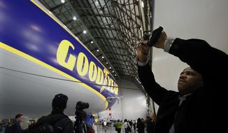 Eddie Rice, right, of Goodyear's Global Engineering department, takes a panoramic photo of Goodyear's  new zeppelin during an exclusive employee preview in the Wingfoot Lake Hangar Friday, March 14, 2014 in Suffield Township, Ohio.  Rice was part of a group of Goodyear employees to get a sneak peak at the zeppelin because they were the first 50 employees to answer five blimp trivia questions correctly during a company wide contest. (AP Photo/Akron Beacon Journal, Karen Schiely)