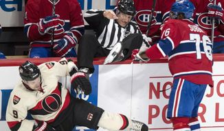 Linesman Brian Pancich, center, goes over the boards after being caught in between Montreal Canadiens' P.K. Subban, right, and Ottawa Senators' Milan Michalek during the first period of an NHL hockey game Saturday, March 15, 2014, in Montreal. (AP Photo/The Canadian Press, Paul Chiasson)