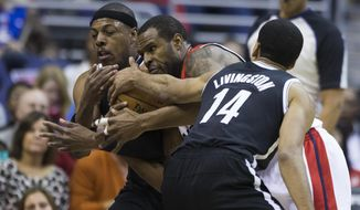 Brooklyn Nets forward Paul Pierce, left, and teammate guard Shaun Livingston, right, try to take the ball away from Washington Wizards forward Trevor Booker during the first half of an NBA basketball game on Saturday, March 15, 2014, in Washington. (AP Photo/ Evan Vucci)
