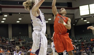 Stephen F. Austin's Jason Martin (21) shoots over the outstretched hands of Stephen F. Austin's Jacob Parker (34) during the first half of an NCAA college basketball game in the championship of the Southland Conference tournament Saturday, March 15, 2014, in Katy, Texas. (AP Photo/Bob Levey)