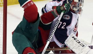 Minnesota Wild's Matt Cooke, left, topples over Columbus Blue Jackets goalie Sergei Bobrovsky, of Russia, in the first period of an NHL hockey game, Saturday, March 15, 2014, in St. Paul, Minn. (AP Photo/Jim Mone)