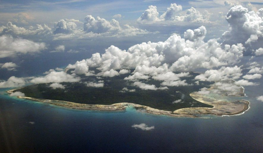 In this Nov. 14, 2005, file photo, clouds hang over the North Sentinel Island, in India's southeastern Andaman and Nicobar Islands. India used heat sensors on flights over hundreds of uninhabited Andaman Sea islands Friday, March 14, 2014, and will expand its search for the missing Malaysia Airlines jet farther west into the Bay of Bengal, officials said. The Indian-controlled archipelago that stretches south of Myanmar contains 572 islands covering an area of 720-by-52 kilometers. Only 37 are inhabited, with the rest covered in dense forests. (AP Photo/Gautam Singh, File)