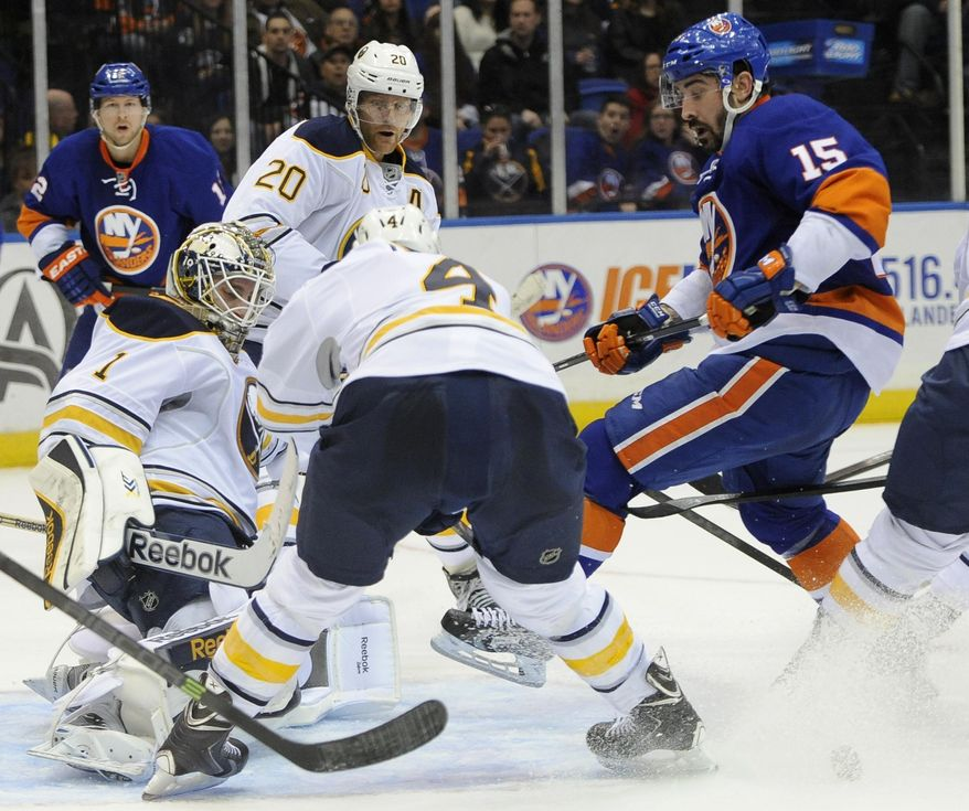Buffalo Sabres goalie Jhonas Enroth (1) blocks a shot on goal by New York Islanders' Cal Clutterbuck (15) as Sabres' Henrik Tallinder (20) and Jamie McBain (4) defend in the second period of an NHL hockey game on Saturday, March 15, 2014, in Uniondale, N.Y. (AP Photo/Kathy Kmonicek)